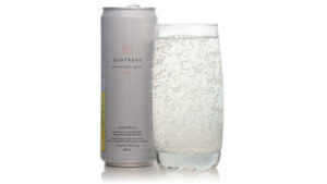 Quatreau can beside clear glass of bubbly water